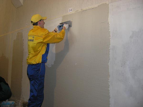 Нанесение штукатурки для выравнивания стен