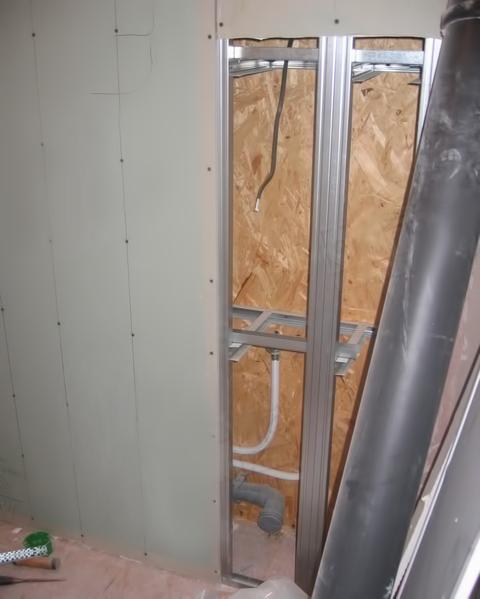 Процесс обшивки фальш-стены в туалете