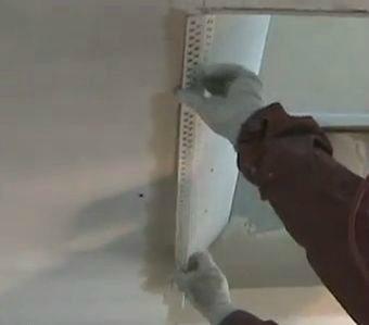 Обработка углов гипсокартона с помощью наклейки пластикового уголка на развернутый угол.